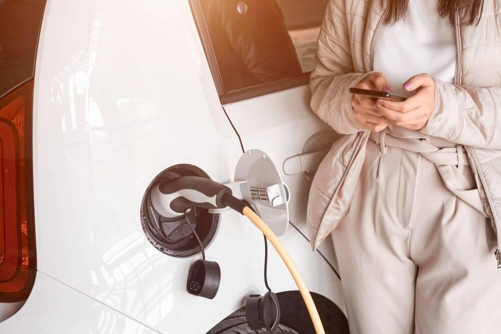 kobieta ładująca samochód elektryczny